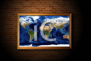 frame with earth map hanging on the brick wall