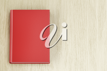 Red book on wooden table, top view