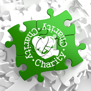 Charity Word Written Arround Icon of Heart in the Hand, Located on Green Puzzle Pieces. Social Concept.
