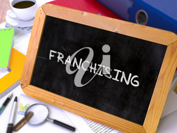 Franchising - Chalkboard with Hand Drawn Text, Stack of Office Folders, Stationery, Reports on Blurred Background. Toned Image. 3d Render.