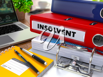 Red Ring Binder with Inscription Insolvent on Background of Working Table with Office Supplies, Laptop, Reports. Toned Illustration. Business Concept on Blurred Background. 3d Render.
