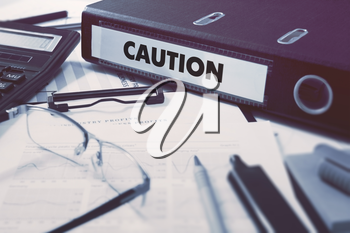 Caution - Ring Binder on Office Desktop with Office Supplies. Business Concept on Blurred Background. Toned Illustration.