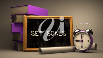 Set Goals - Chalkboard with Hand Drawn Text, Stack of Books, Alarm Clock and Rolls of Paper on Blurred Background. Toned Image. 3D Render.