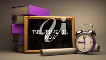 The Time is Now Handwritten on Chalkboard. Time Concept. Composition with Chalkboard and Stack of Books, Alarm Clock and Scrolls on Blurred Background. Toned Image. 3D Render.