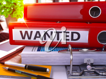 Red Ring Binder with Inscription Wanted on Background of Working Table with Office Supplies and Laptop. Wanted - Toned Illustration. Wanted Business Concept on Blurred Background. 3D Render.