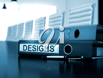 Office Folder with Inscription Designs on Black Table. Designs. Concept on Blurred Background. Designs - File Folder on Working Table. Designs - Business Concept on Blurred Background. 3D.