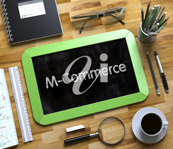 M-Commerce Handwritten on Green Small Chalkboard. Top View of Wooden Office Desk with a Lot of Business and Office Supplies on It. M-Commerce on Small Chalkboard. 3d Rendering.