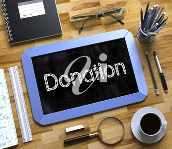 Small Chalkboard with Donation Concept. Donation Handwritten on Blue Small Chalkboard. Top View of Wooden Office Desk with a Lot of Business and Office Supplies on It. 3d Rendering.