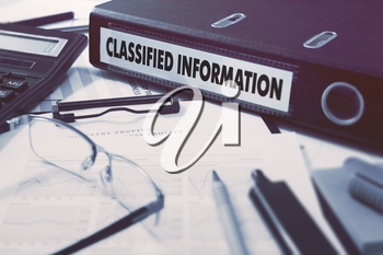 Classified Information - Ring Binder on Office Desktop with Office Supplies. Business Concept on Blurred Background. Toned Illustration.