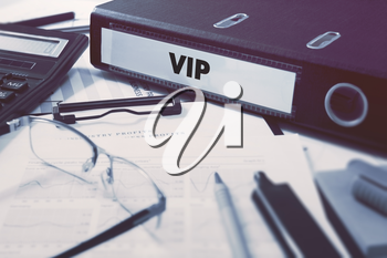 Ring Binder with inscription VIP - Very Important Person - on Background of Working Table with Office Supplies, Glasses, Reports. Toned Illustration. Business Concept on Blurred Background.