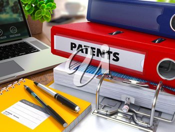 Red Ring Binder with Inscription Patents on Background of Working Table with Office Supplies, Laptop, Reports. Toned Illustration. Business Concept on Blurred Background.