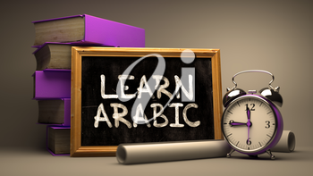 Hand Drawn Motivational Quote - Learn Arabic - on Chalkboard. Blurred Background. Toned Image.