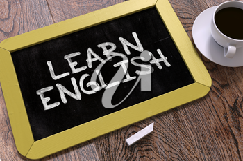 Learn English. Motivational Quote Handwritten on Yellow Chalkboard. Business Concept. Composition with Chalkboard and Cup of Coffee. Top View Image.