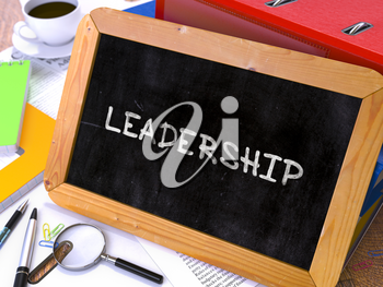 Handwritten Leadership on a Chalkboard. Composition with Chalkboard and Ring Binders, Office Supplies, Reports on Blurred Background. Toned Image.