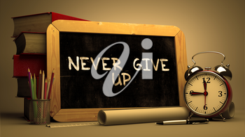 Never Give Up Handwritten by white Chalk on a Blackboard. Composition with Small Chalkboard and Stack of Books, Alarm Clock and Rolls of Paper on Blurred Background. Toned Image.