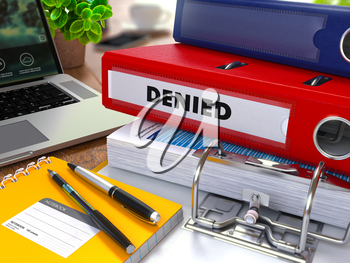 Red Ring Binder with Inscription Denied on Background of Working Table with Office Supplies, Laptop, Reports. Toned Illustration. Business Concept on Blurred Background.