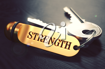Keys and Golden Keyring with the Word Strength over Black Wooden Table with Blur Effect. Toned Image.
