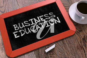 Business Education - Red Chalkboard With Hand Drawn Text and White Cup of Coffee on Wooden Table. Top View.
