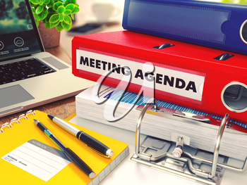 Meeting Agenda - Red Office Folder on Background of Working Table with Stationery, Laptop and Reports. Business Concept on Blurred Background. Toned Image.