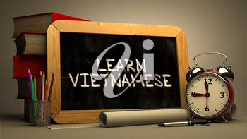 Learn Vietnamese - Chalkboard with Hand Drawn Motivational Quote, Stack of Books, Alarm Clock and Rolls of Paper on Blurred Background. Toned Image.