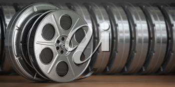 Video, cinema, movie, multimedia concept. A row of vintage film reel or  film spools with filmstrip  3d illustration