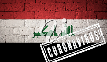 Flag of the Iraq with original proportions. stamped of Coronavirus. brick wall texture. Corona virus concept. On the verge of a COVID-19 or 2019-nCoV Pandemic.