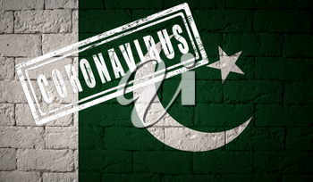 Flag of the Pakistan with original proportions. stamped of Coronavirus. brick wall texture. Corona virus concept. On the verge of a COVID-19 or 2019-nCoV Pandemic.