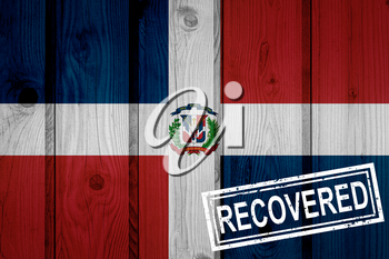 flag of Dominican Republic that survived or recovered from the infections of corona virus epidemic or coronavirus. Grunge flag with stamp Recovered