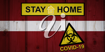 Flag of the Latvia in original proportions. Quarantine and isolation - Stay at home. flag with biohazard symbol and inscription COVID-19.