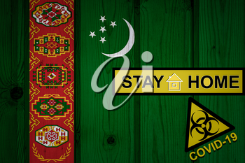 Flag of the Turkmenistan in original proportions. Quarantine and isolation - Stay at home. flag with biohazard symbol and inscription COVID-19.
