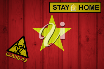 Flag of the Vietnam in original proportions. Quarantine and isolation - Stay at home. flag with biohazard symbol and inscription COVID-19.